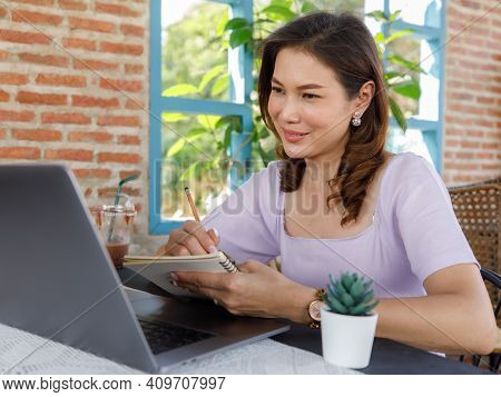 Cute Beautiful Middle-aged Asian Woman Sitting In Shop And Using A Pencil To Write On A Paper Notebo