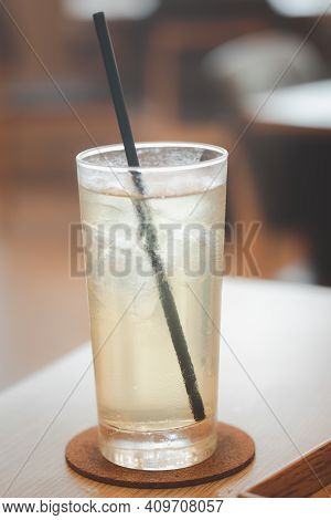 Iced Green Tea With Black Straw On Wood Table