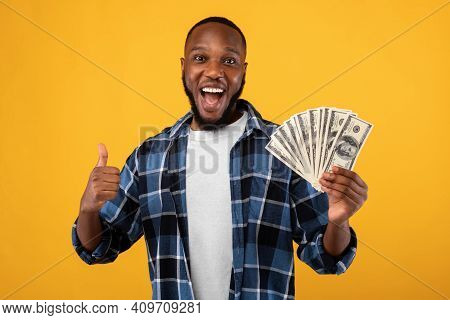 Big Luck. Joyful Black Guy Holding Money Cash Gesturing Thumbs Up Posing Standing Over Yellow Studio