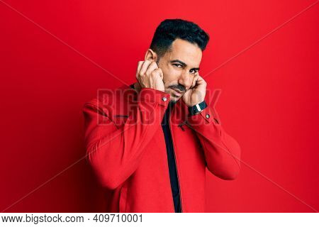 Young hispanic man wearing red leather jacket covering ears with fingers with annoyed expression for the noise of loud music. deaf concept.