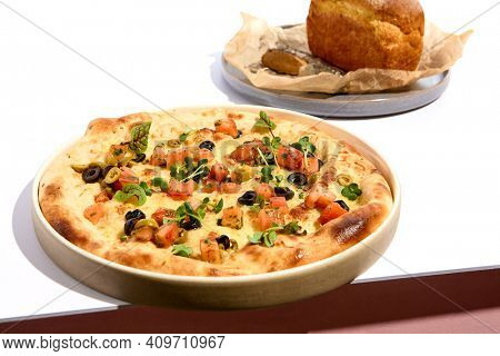 Olives and TOmato Focaccia and Cornbread on white table. White table and pink wall in sunlight with hard shadow. Summer day food concept