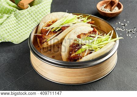 Bao bun with hoisin chicken. Bamboo steamer on dark slate table. Chinese, asian, authentic food concept.