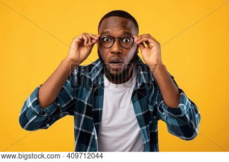 Amazed Black Man Wearing Eyeglasses Looking At Camera Through Glasses Standing Posing On Yellow Stud