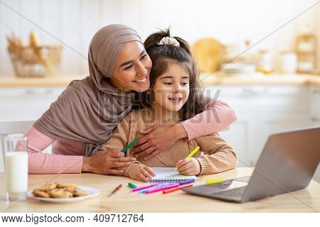 Happy Muslim Mom In Hijab And Her Little Daughter Using Laptop In Kitchen, Having Fun Together At Ho