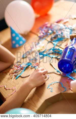 Close Up Of Hand Woman Hold A Glass Of Champagne, Sleeping At Table In Messy Room After Birthday Par