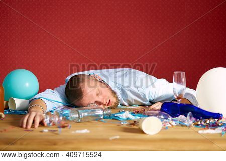 Bearded Man Sleeping At Table In Messy Room After Bachelor Party