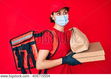 Young hispanic woman wearing medical mask holding take away food smiling looking to the side and staring away thinking.