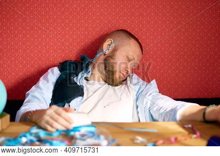 Bearded Man Sleeping At Table In Messy Room With Girls Underwear, Brassiere After Bachelor Party