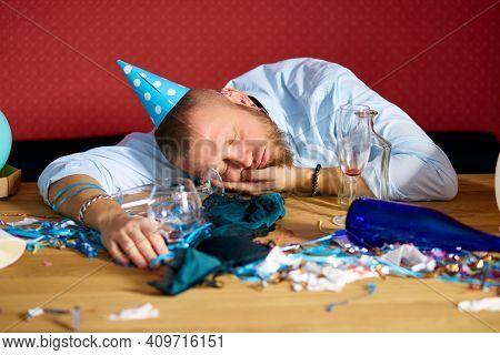 Man Sleeping At Table With Blue Cap In Messy Room After Birthday Party