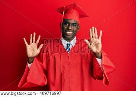 Young african american man wearing graduation cap and ceremony robe showing and pointing up with fingers number ten while smiling confident and happy.