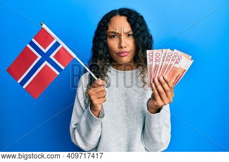 Young latin woman holding norway flag and norwegian krone banknotes skeptic and nervous, frowning upset because of problem. negative person.