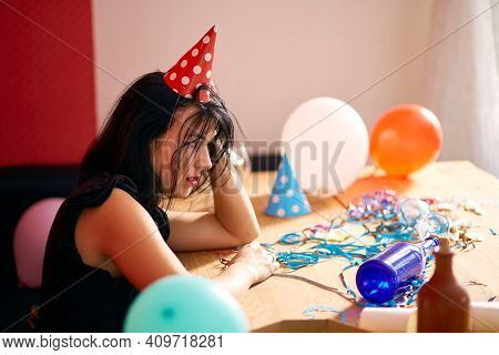 Young Woman With Red Rubbed Lipstick And Cap, Sitting Tired At Table In Messy Room After Birthday Pa