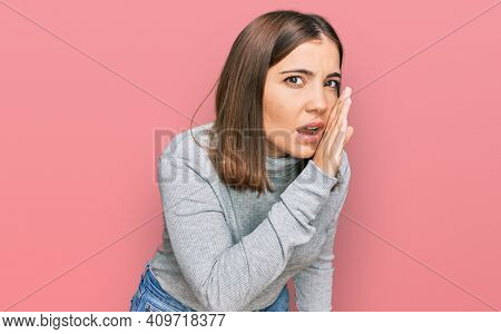 Young beautiful woman wearing casual turtleneck sweater hand on mouth telling secret rumor, whispering malicious talk conversation