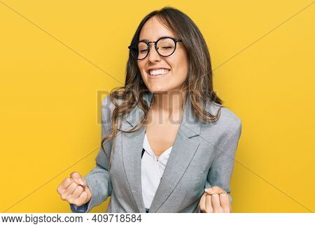 Young brunette woman wearing business clothes very happy and excited doing winner gesture with arms raised, smiling and screaming for success. celebration concept.