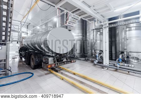 Dairy Factory Industry, Milk Tanker Truck Pumps Products Into Steel Storage Tanks