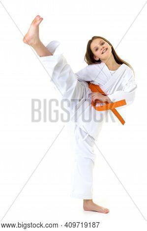 Happy Girl In Kimono Training Karate. Smiling Teenage Girl Dressed Sportswear With Orange Belt Exerc