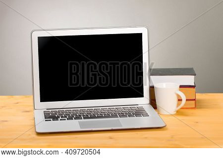 Laptop With Blank Screen, Cup Of Coffee And Books Or Notebooks On A Wooden Table. Mockup For Your Te