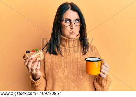 Middle age brunette woman eating pastry and drinking coffee puffing cheeks with funny face. mouth inflated with air, catching air.