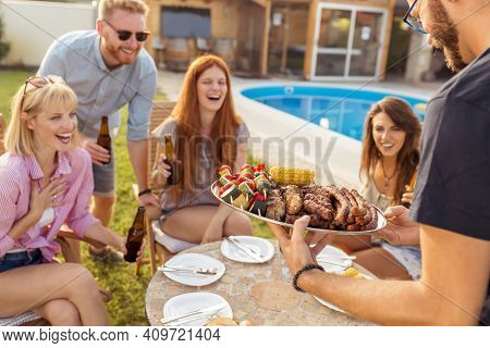 Group Of Cheerful Young Friends Gathered Around The Table, Drinking Beer And Having Fun At A Backyar