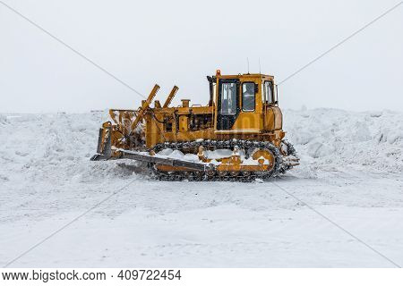 Yellow Bulldozer Removes Snowdrifts In A Severe Blizzard At Winter