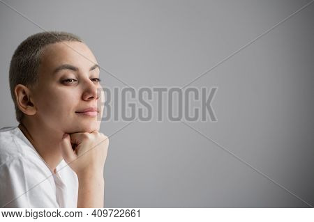 Portrait Of Pensive Young Woman With Short Hair On White Background. Copy Space