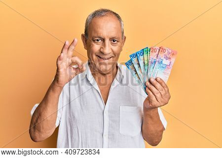 Handsome mature senior man holding swiss franc banknotes doing ok sign with fingers, smiling friendly gesturing excellent symbol