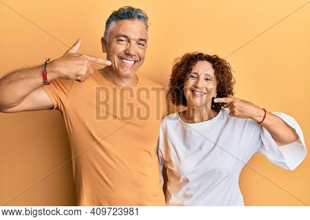 Beautiful middle age couple together wearing casual clothes smiling cheerful showing and pointing with fingers teeth and mouth. dental health concept.
