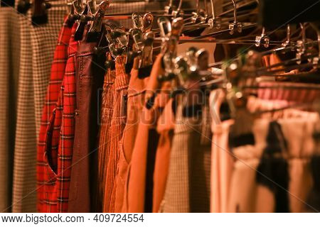 Womens Brown And Red Trousers In A Row Hung On A Hanger In The Closet