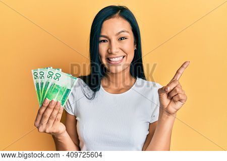 Beautiful hispanic woman holding 50 norwegian krone banknotes smiling happy pointing with hand and finger to the side