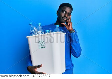 Young african american man holding recycling wastebasket with plastic bottles serious face thinking about question with hand on chin, thoughtful about confusing idea