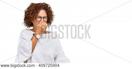 Beautiful middle age mature woman wearing casual clothes and glasses smelling something stinky and disgusting, intolerable smell, holding breath with fingers on nose. bad smell