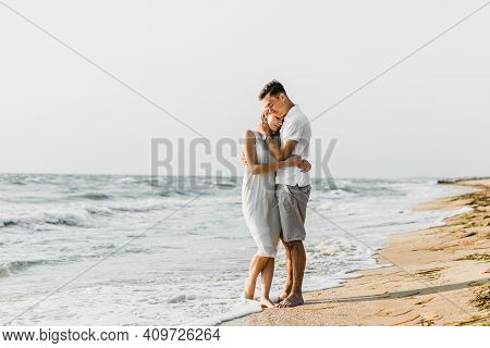 Beautiful Loving Couple Walks On The Seashore. Happy Young Couple Spend Time On The Beach. Honeymoon