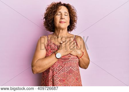 Beautiful middle age mature woman wearing summer dress smiling with hands on chest with closed eyes and grateful gesture on face. health concept.