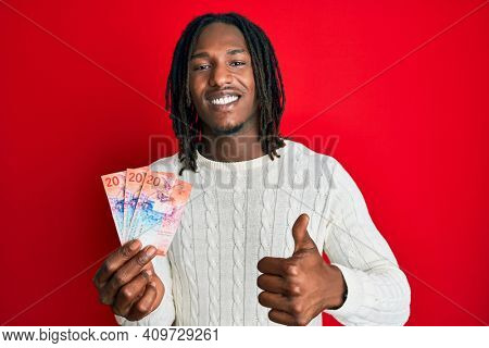 African american man with braids holding 20 swiss franc banknotes smiling happy and positive, thumb up doing excellent and approval sign