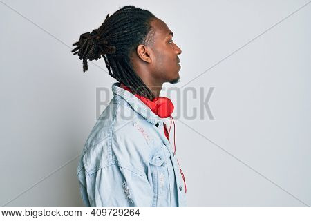African american man with braids listening to music using headphones looking to side, relax profile pose with natural face with confident smile.