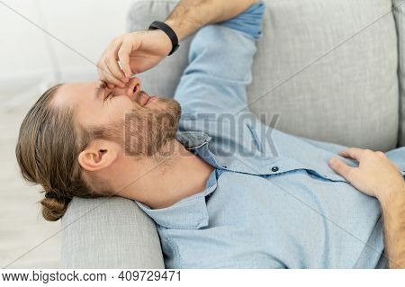 Attractive Man With Light Brown Hair Pulled Back, Beard, Lying On The Grey Cozy Couch, With Pleasure