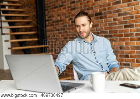 Relaxed Successful Employee Working In The Modern Office, At The Desk, Typing On The Laptop, On A Br