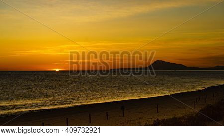 Sunrise Over Sea. View From Gandia Beach, Valencia Spain. Montgo Mountain Massif Silhouetted On Hori