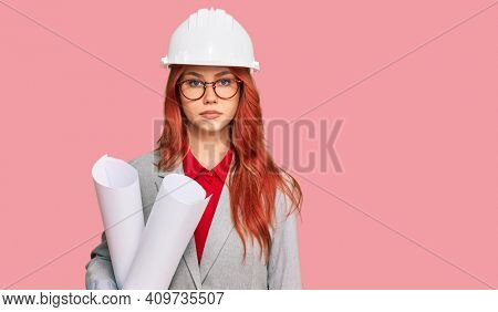 Young redhead architect woman wearing safety helmet holding blueprints thinking attitude and sober expression looking self confident