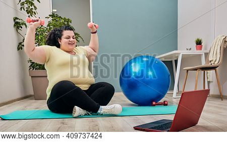 Overweight Woman Doing Exercises At Home With Online Personal Trainer For Weight Loss Using Dumbbell