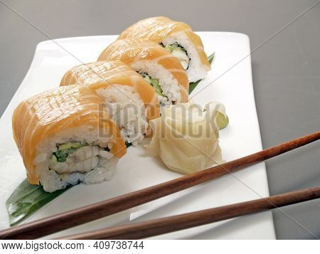Sushi. California, Rainbow Rolls With Salmon, Pickled Ginger, Chopsticks On A White Plate.