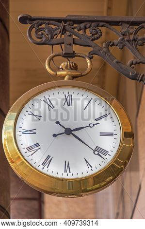 Gold Clock With Illuminated White Dial Hanging