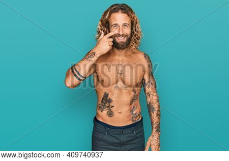 Handsome man with beard and long hair standing shirtless showing tattoos pointing with hand finger to face and nose, smiling cheerful. beauty concept