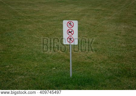 Do Not Walk The Dog On The Grass . Do Not Walk On The Grass Sign In The Park . You Can't Ride A Bike