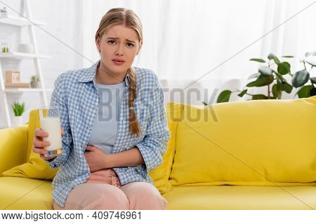 Exhausted Woman With Lactose Intolerance Holding Glass Of Milk On Couch.