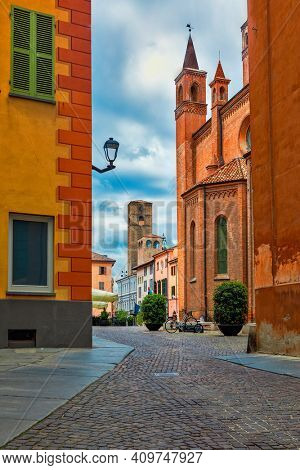 Narrow cobblestone street, San Lorenzo cathedral and medieval tower on background in old town of Alba, in Piedmont, Northern Italy.