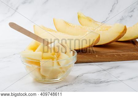 Sliced To Pieces Of Melon. Melon Cut In A Bowl On A Light Background With Copy Space.