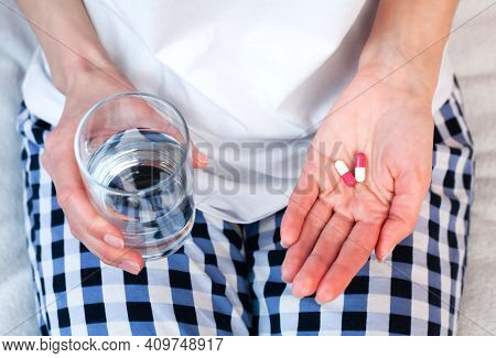 Young Woman Holds Two Pills And Glass Of Water In Hands. Taking Vitamins, Supplements, Antibiotic, A
