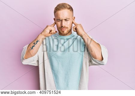 Young caucasian man wearing casual clothes covering ears with fingers with annoyed expression for the noise of loud music. deaf concept.