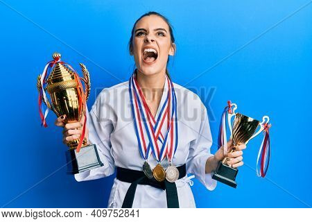 Beautiful brunette young woman wearing karate fighter uniform and medals holding trophy angry and mad screaming frustrated and furious, shouting with anger looking up.